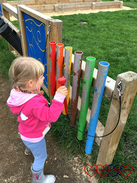 Sophie playing with the musical tubes in the play area of a local country park