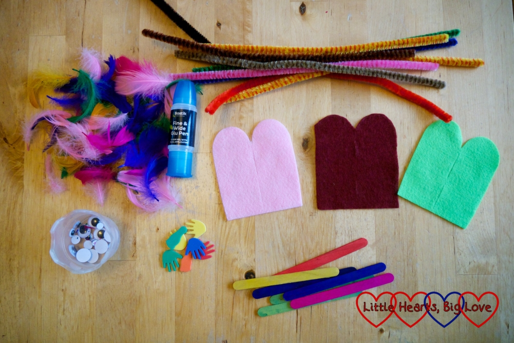 Feathers, pipe cleaners, googly eyes, foam hands and feet, craft sticks, felt shapes and a Bostik Fine and Wide Glu Pen on a table