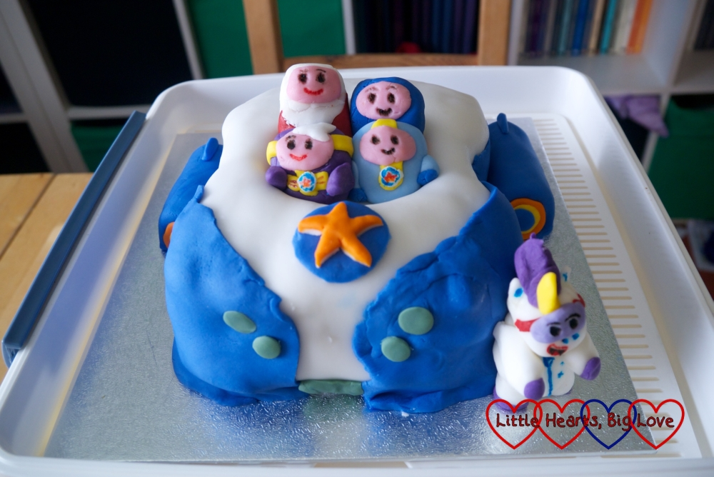 A Go-Jetters Vroomster cake with the four Go Jetters sitting inside the vroomster and Ubercorn standing next to it