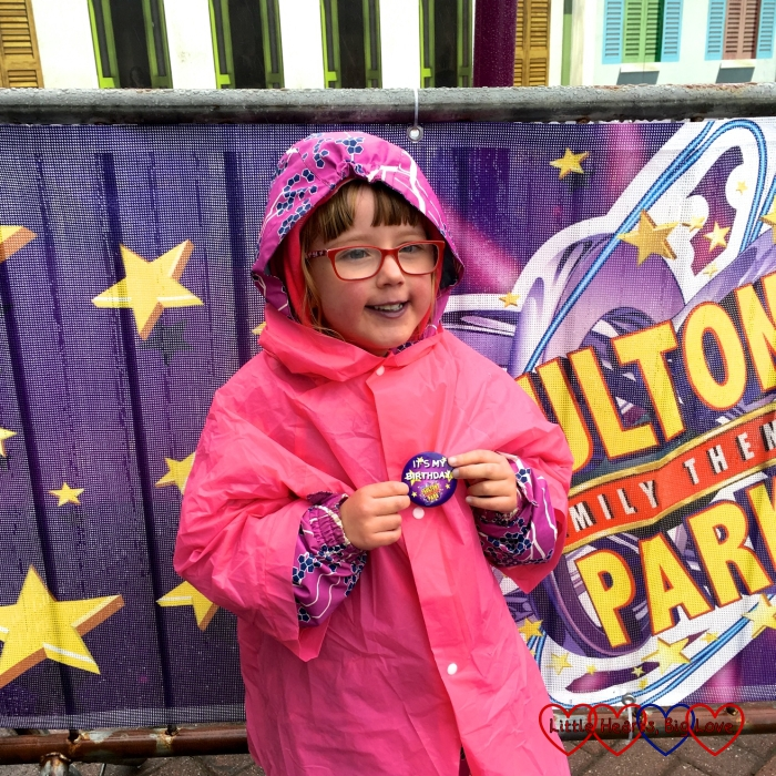 Jessica wearing her birthday badge and standing by a Paultons Park banner