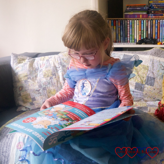 Jessica wearing a princess dress and looking at an issue of Storytime