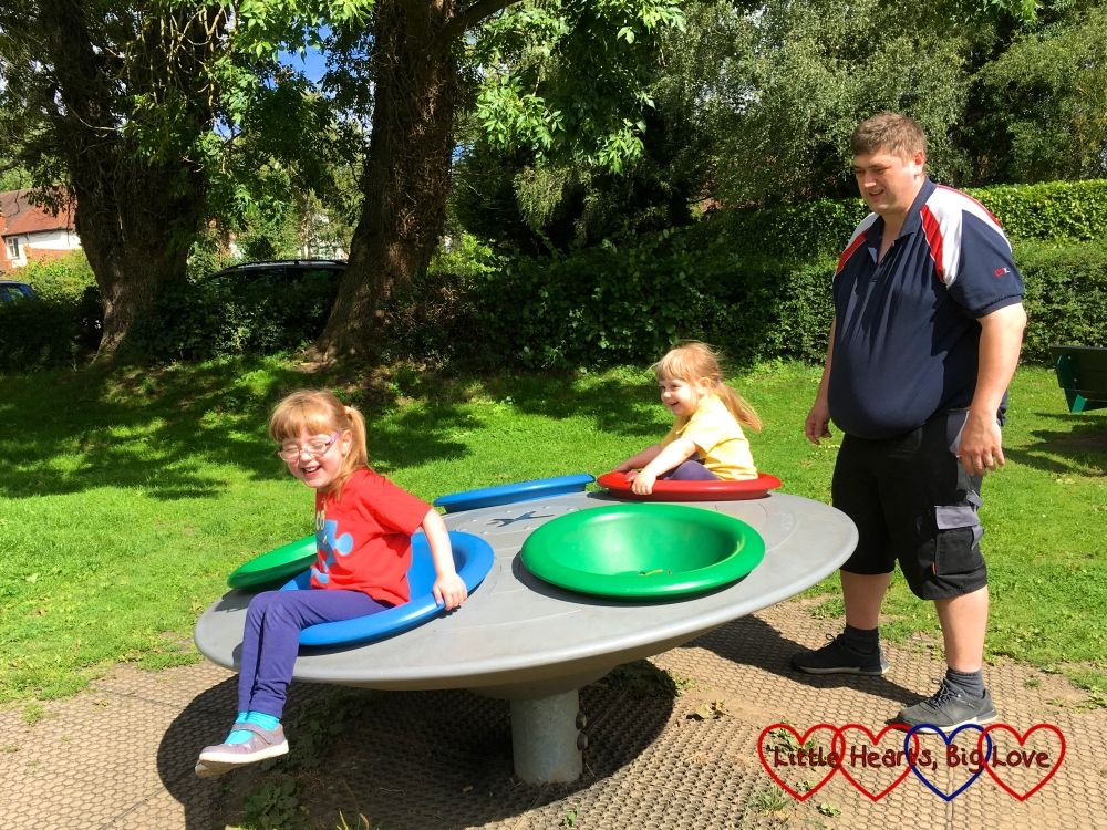 Jessica and Sophie being spun by Daddy on the roundabout at the playground in Seer Green