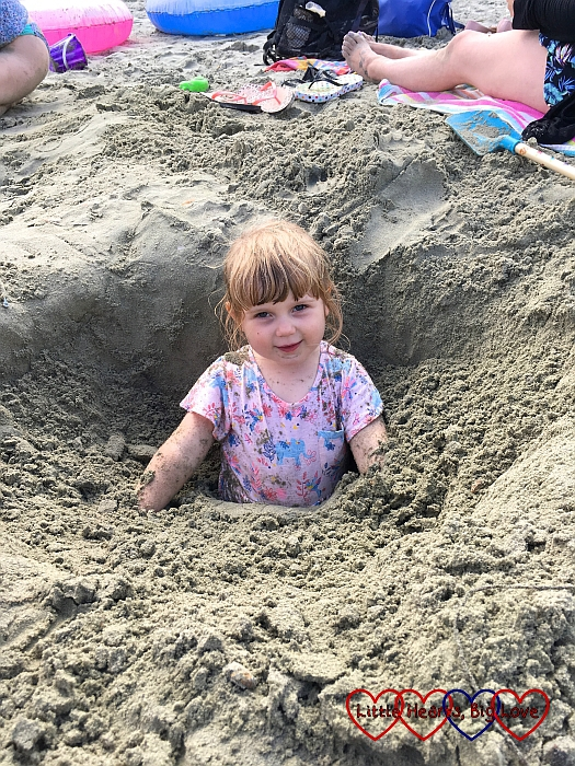 Sophie getting buried in the sand while standing the hole we dug