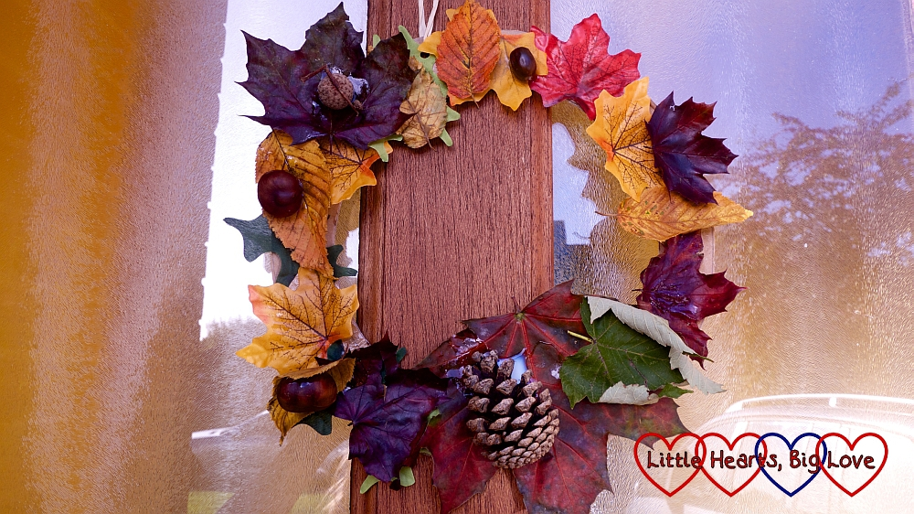 An autumn wreath made with colourful leaves, conkers and a pine cone hanging on a door