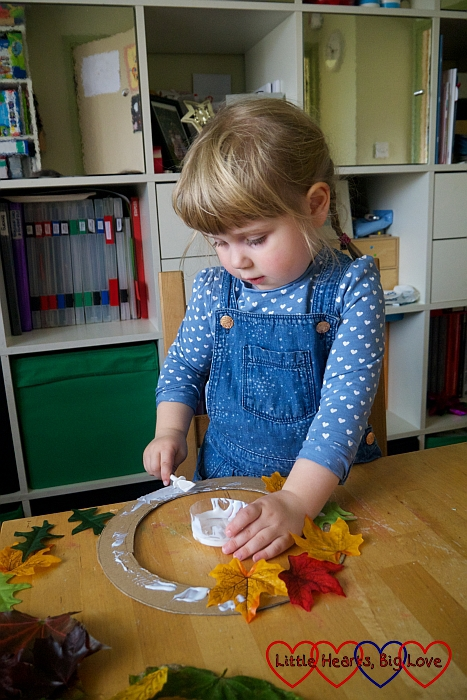 Sophie glueing leaves on to the cardboard ring