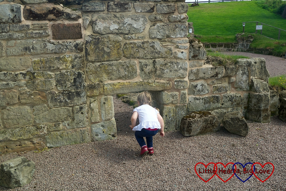 Sophie going through a small doorway in the ruins of Bagot's Castle