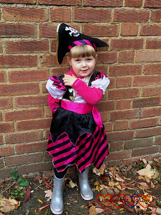 Sophie standing in front of a brick wall, wearing her pirate costume