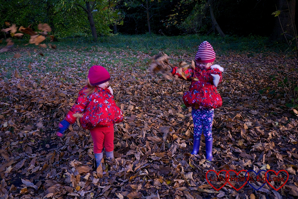 Sophie and Jessica throwing fallen leaves in the air