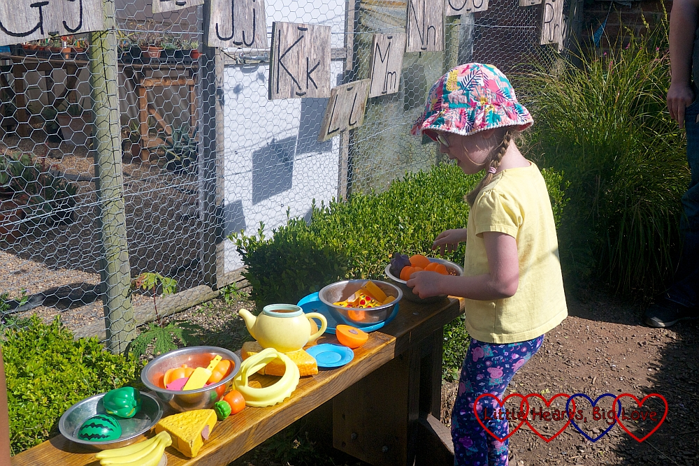 Jessica setting up some play food on a bench outside the play house in the kitchen garden at Packwood House