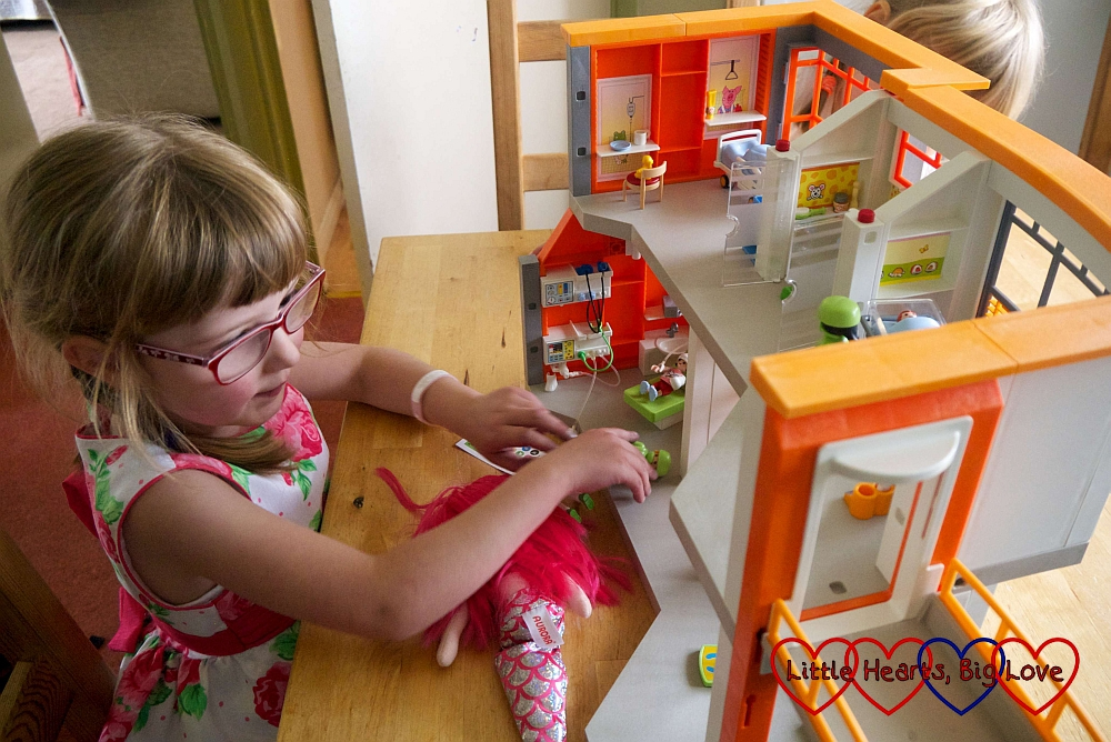Jessica playing with her Playmobil hospital