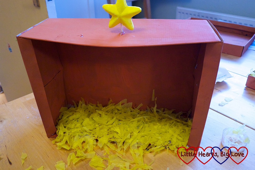 The bottom of the shoebox stable filled with shredded yellow tissue paper