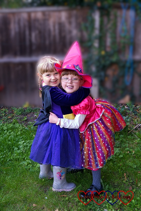 Jessica and Sophie having a cuddle in the garden while wearing their Halloween costumes
