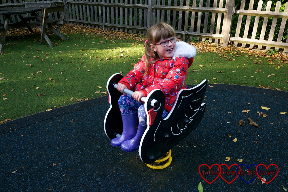 Jessica on one of the rocking black swans in the children's play area