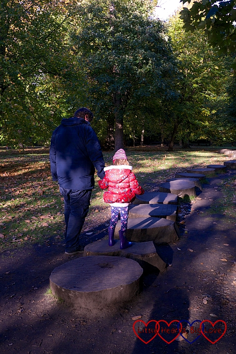 Hubby holding Jessica's hand to help her walk along the natural stepping stones near the ha-ha at Claremont Landscape Garden