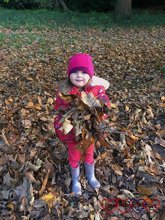 Sophie holding a pile of leaves ready to throw in the air