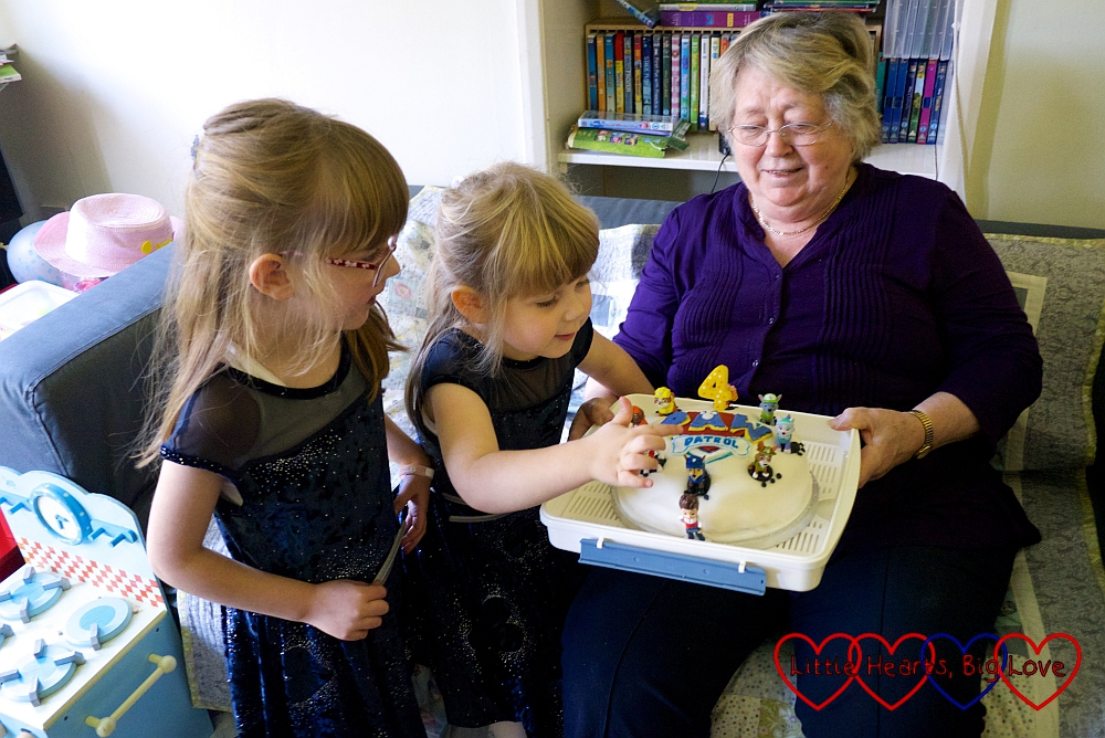 Sophie and Jessica looking at Sophie's Paw Patrol birthday cake which Grandma is holding