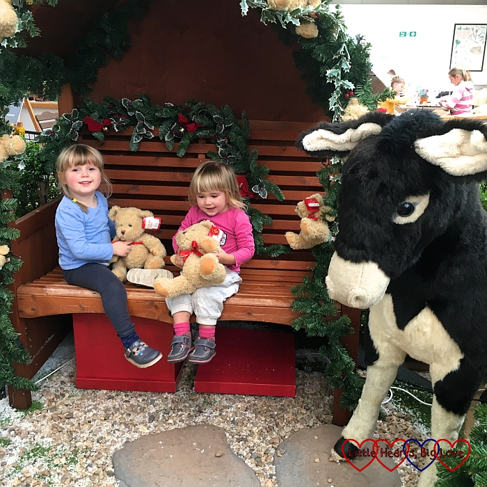 Sophie with her friend sitting on a bench next to a donkey in one of the Christmas displays