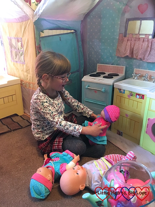 Jessica playing with a dolly in the Rose Petal Cottage playhouse