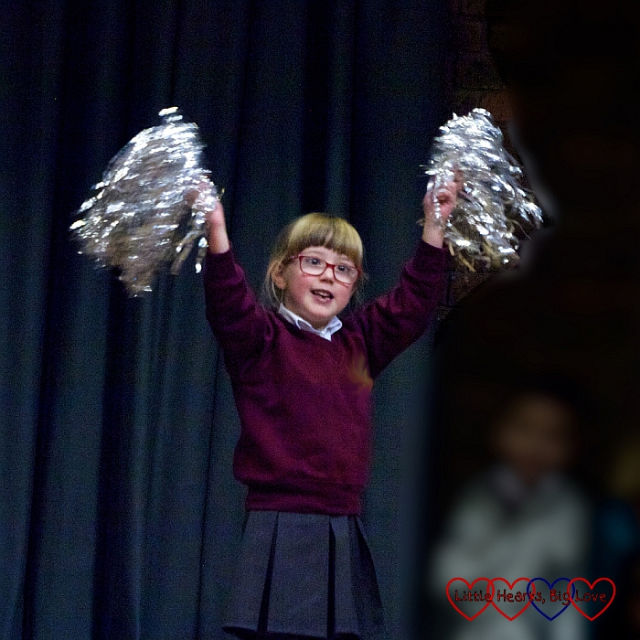 Jessica holding silver pompoms while performing in her class assembly