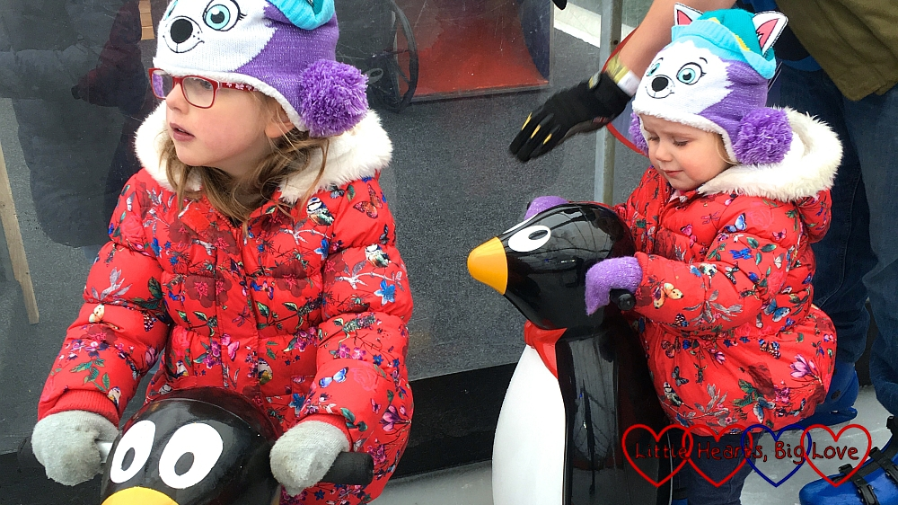 Jessica and Sophie holding on to penguin skate aids at the Windsor on Ice temporary ice rink