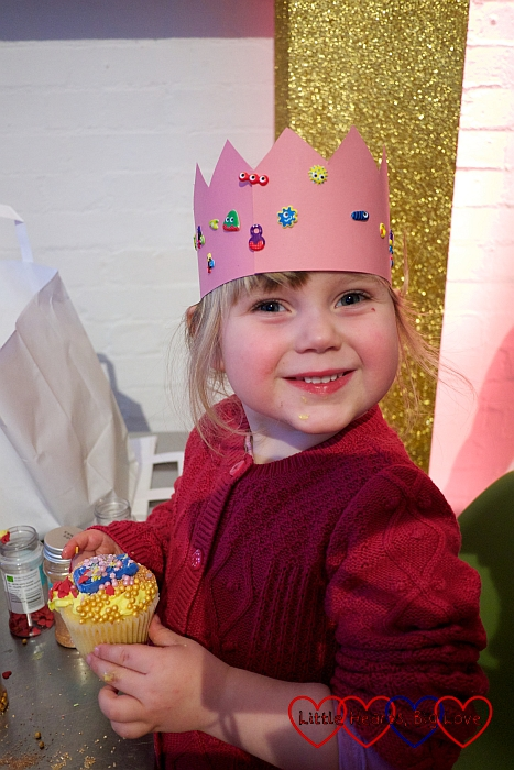 Sophie wearing her paper crown and holding her decorated cupcake
