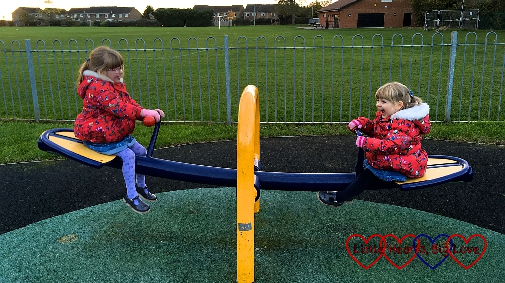 Jessica and Sophie on a seesaw at the park