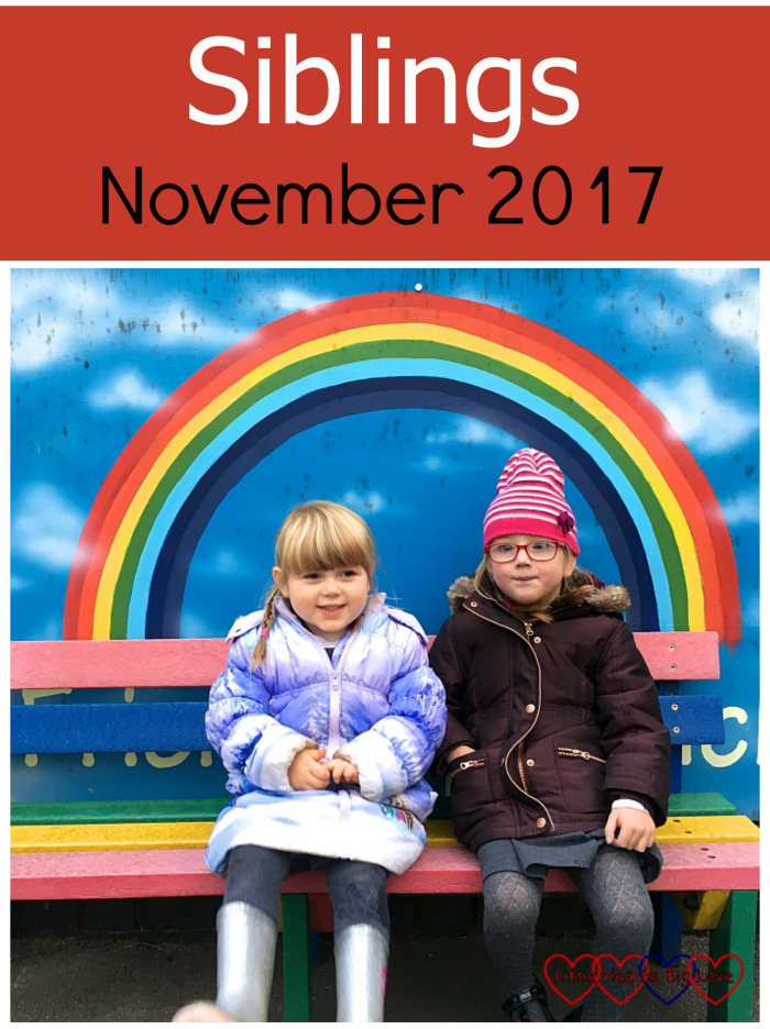 "Jessica and Sophie sitting on the friendship bench at school with a painted rainbow behind them - ""Siblings - November 2017"""