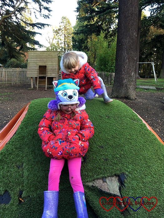 Jessica and Sophie climbing the mound over the play tunnel at Langley Park