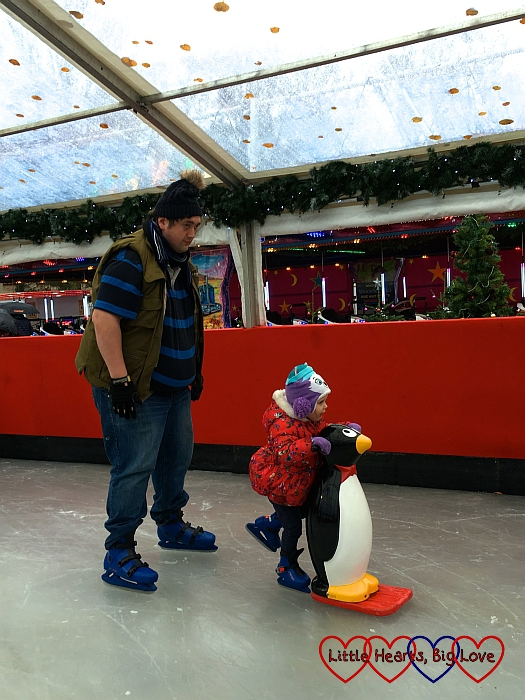 Hubby skating with Sophie pushing a penguin skate aid in front of him