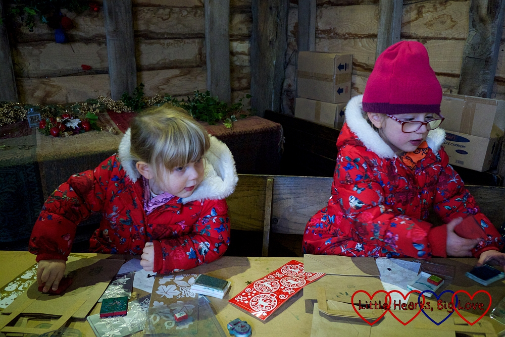Jessica and Sophie decorating a paper bag in the Northolt Barn
