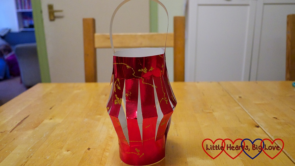 A red paper lantern with gold glitter decoration