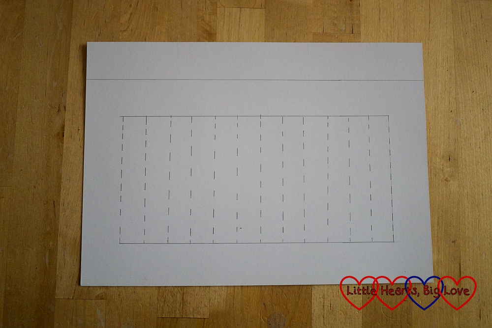 A template for the Chinese paper lantern showing a strip of paper at the top for the handle and vertical lines for the slits in the lantern