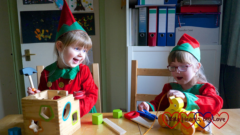 Jessica and Sophie dressed as elves pretending to make wooden toys