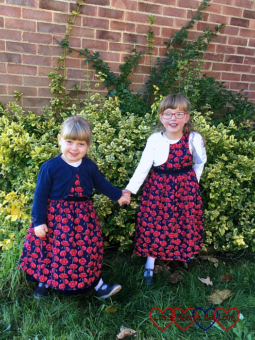 Jessica and Sophie wearing their pretty poppy-print dresses from Seesaw children's clothes