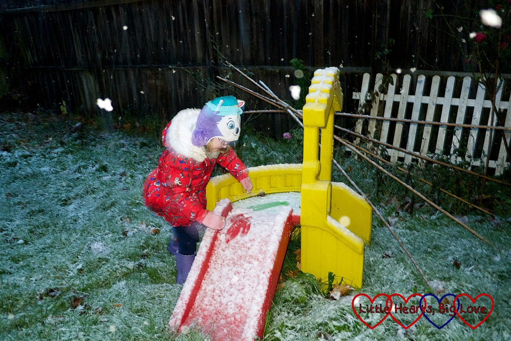 Jessica scooping snow off the slide in the garden