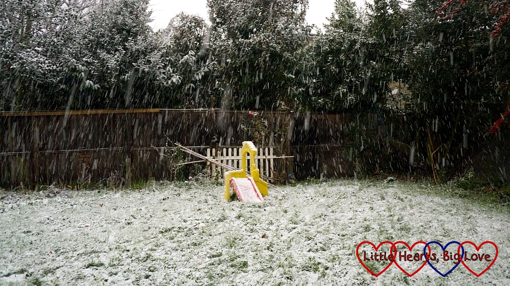 My back garden with the snow falling on it