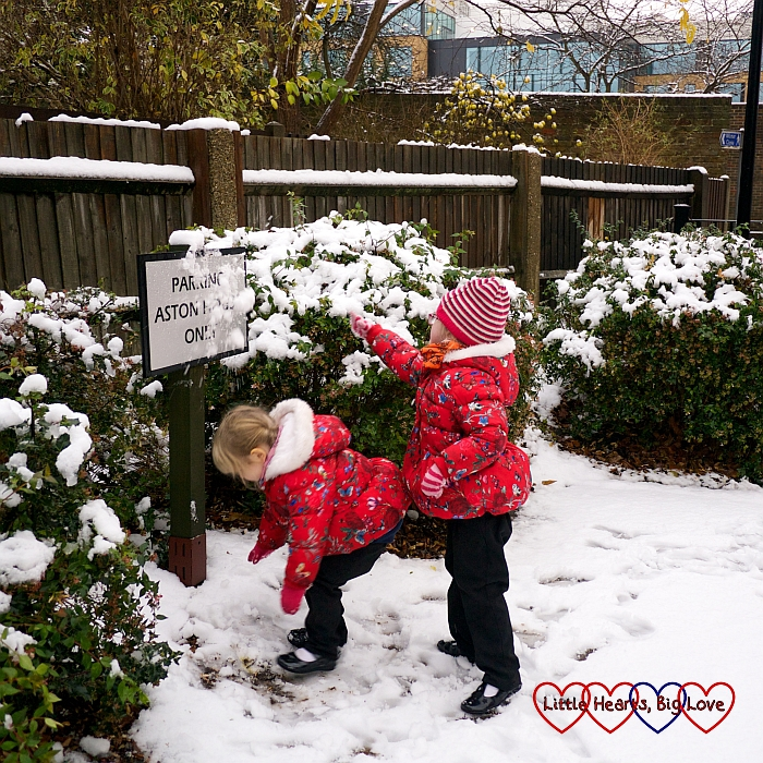 Sophie and Jessica throwing snowballs at a sign
