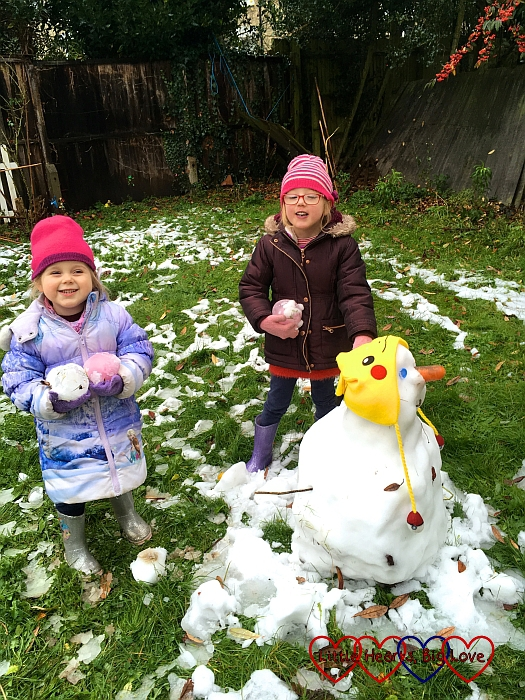 "Sophie and Jessica standing next to the snowman, holding ""ice diamonds"""