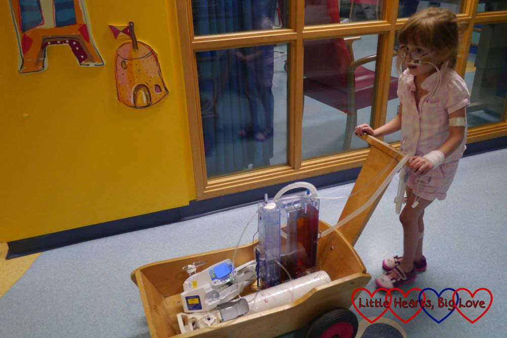 Jessica pushing her drains and pumps in a trolley on her first walk around the ward post-op