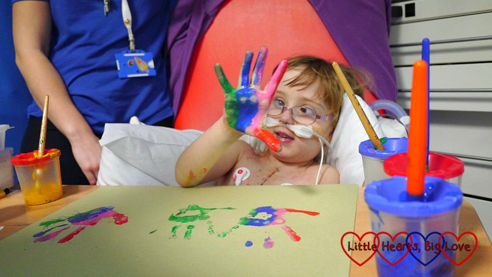 Jessica holding up a paint-covered hand while sitting out in a chair next to her hospital bed