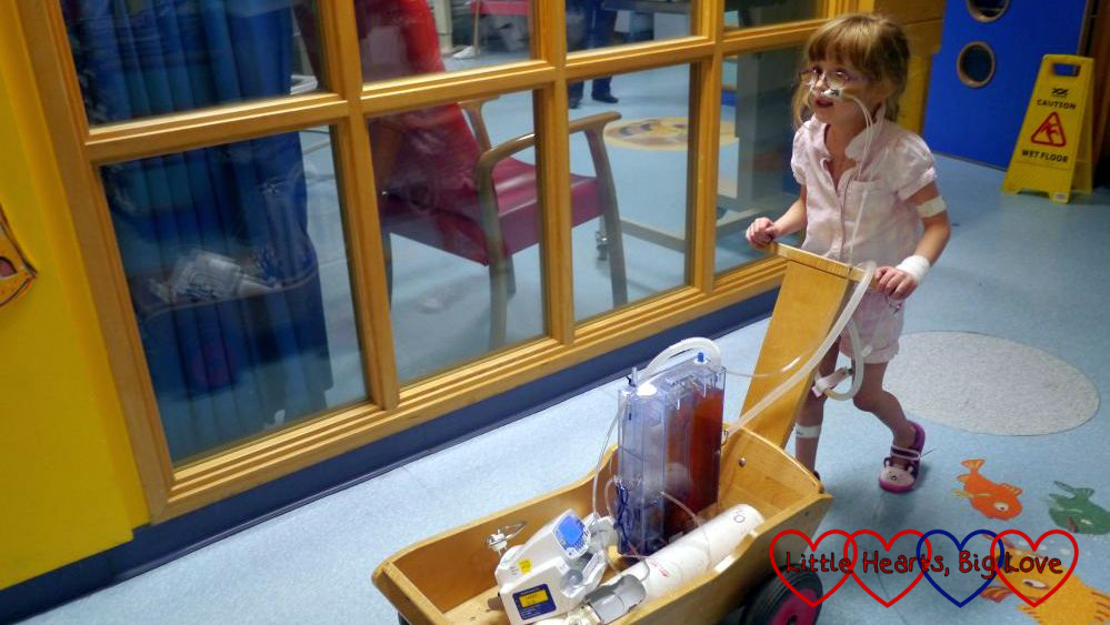 Jessica pushing her chest drain, oxygen and heparin pump in a trolley on her first post-op walk around the ward