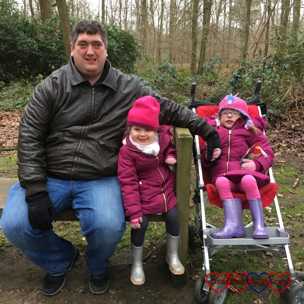 Hubby and Sophie sitting on a bench, holding hands with Jessica in her buggy