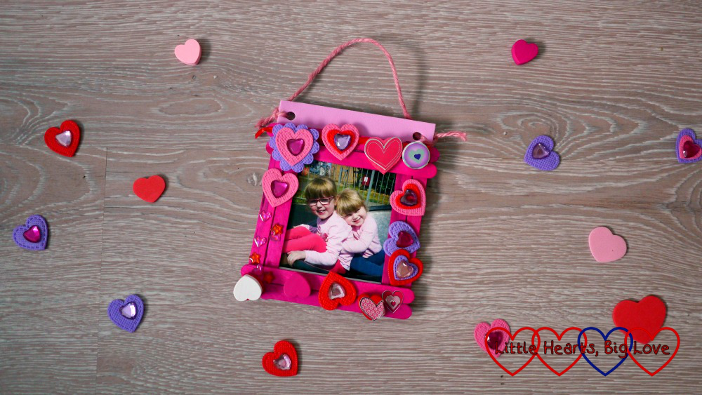 The finished craft stick photo frame surrounded by heart shapes