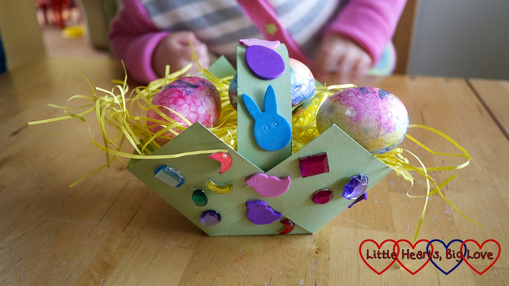 The finished basket filled with shredded tissue paper and painted eggs