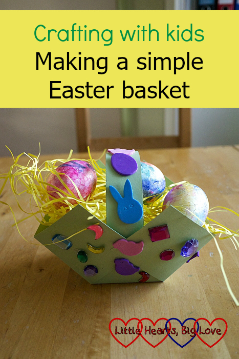 A decorated cardboard Easter basket filled with painted polystyrene eggs