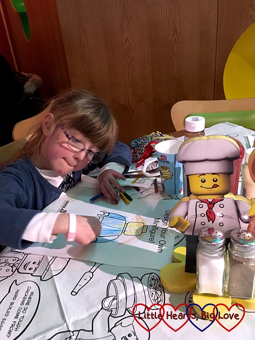 Jessica colouring in her Minifigures colouring sheet at the Bricks restaurant