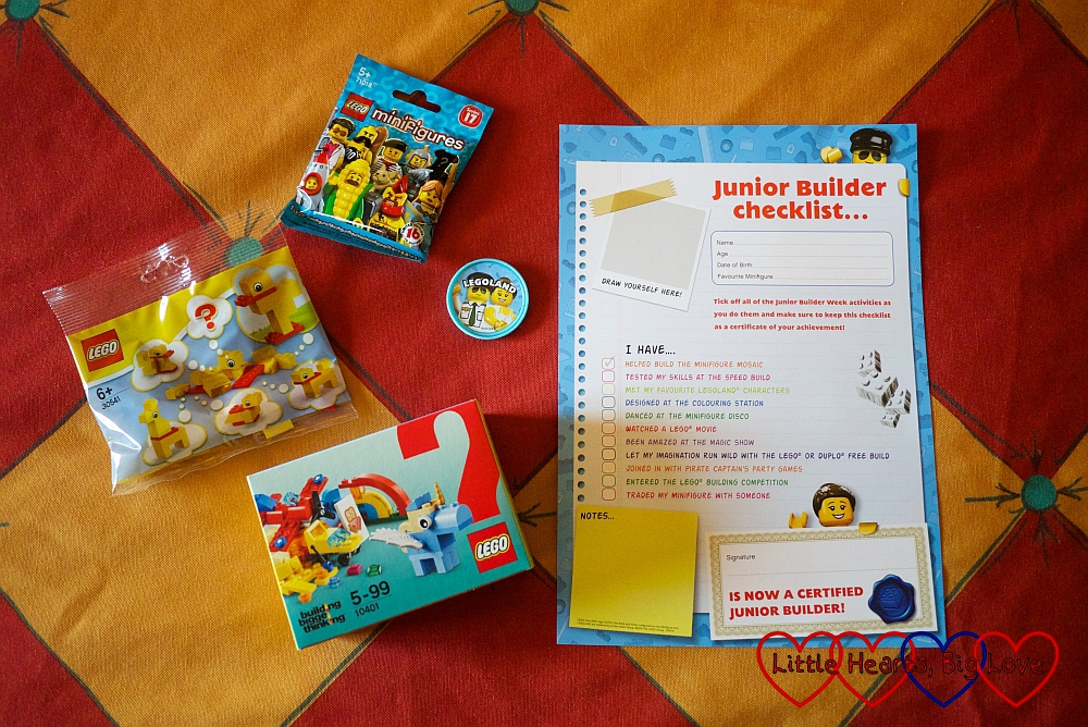The contents of the girls' welcome bags - two Lego sets, a Minifigures blind bag, a pop badge and the Junior Builders Week checklist