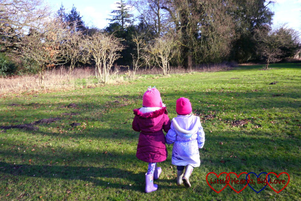 Jessica and Sophie walking hand-in-hand across a meadow