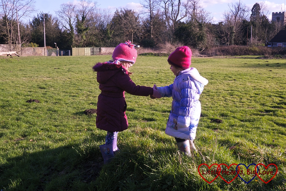 Sophie holding Jessica's hand and helping her over one of the mounds