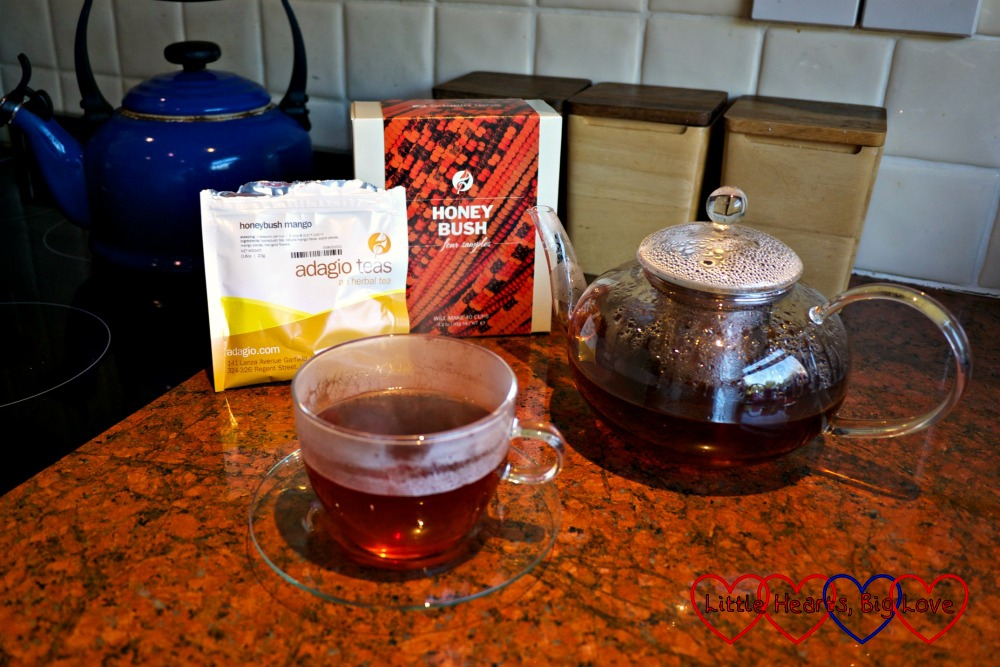 Honeybush Mango tea brewing in the glass teapot with a glass cup and saucer containing honeybush tea